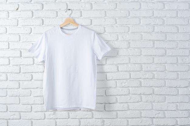 Weißes t-shirt, das auf kleiderbügel gegen mauer hängt