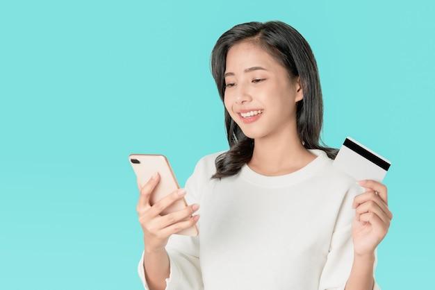 Weißes t-shirt der asiatinnen des lächelns glücklich, das den smartphone und kreditkarte online kaufen hält