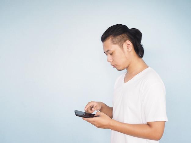 Weißes t-shirt der asiatischen jungen hippie-mannabnutzung, das handy spielt