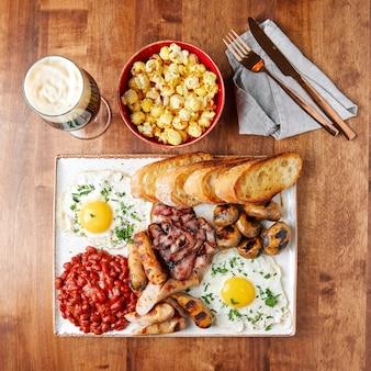 Weißes tablett mit essen, würstchen, speck, bohnen, fleischbällchen, rührei mit gemüse, kwas, geröstetem weißbrot, bier in einem glasbecher, schüssel popcorn