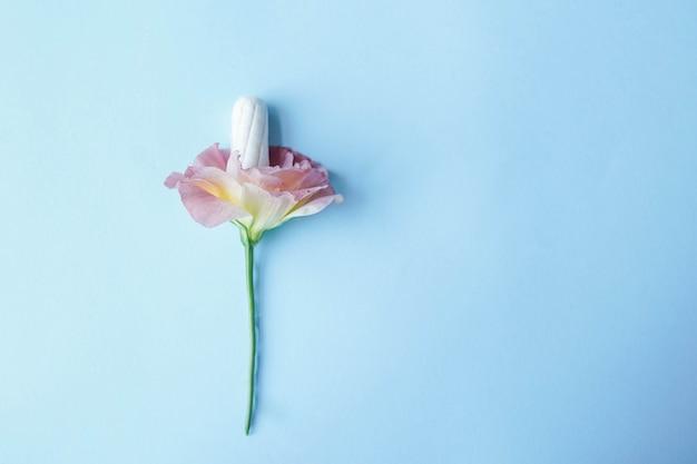 Weißes tampoo mit rosa blume auf blauem hintergrund