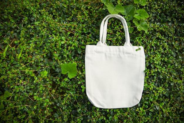 Weißes taschesegeltuchgewebe eco taschenstoff-einkaufssack auf grünem blattnaturhintergrund