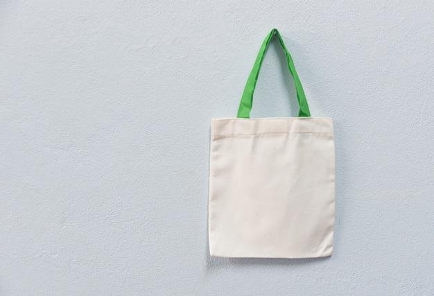 Weißes taschesegeltuchgewebe eco taschenstoff-einkaufssack auf wandhintergrund