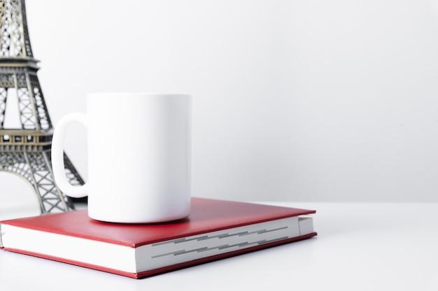 Weißes tassenmodell mit arbeitsplatzzubehör auf weißem tisch