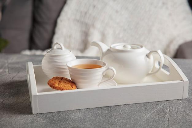 Weißes teeservice und kuchen auf grauem holztisch. weißes holztablett mit tassen, teekanne und girlandenlichtern.