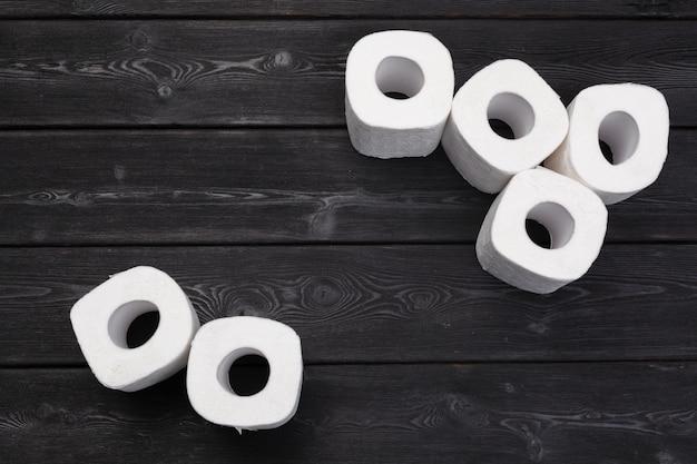 Weißes toilettenpapier rollt auf schwarzem hölzernem hintergrund