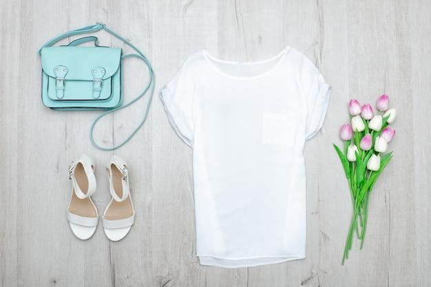 Weißes top, weiße schuhe und eine minztüte. modisches konzept. holzuntergrund
