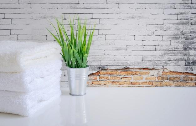 Weißes tuch und houseplant auf weißer tabelle mit alter backsteinmauer