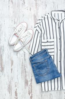 Weißes und blau gestreiftes hemd, weiße turnschuhe und jeans. modisches konzept