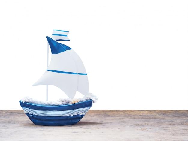 Weißes und blaues segelbootspielzeug auf holz