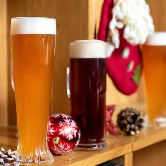 Weißes und dunkles bier trinken gläser, tassen mit weihnachten, neujahrsspielzeug, dekorationen, geschenke