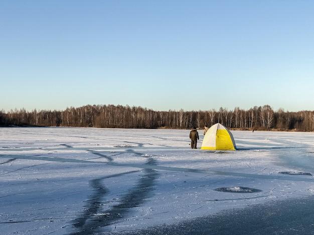 Weißes und gelbes touristenzelt und zwei fischer auf dem eisbedeckten leeren see. eisfischen im winter