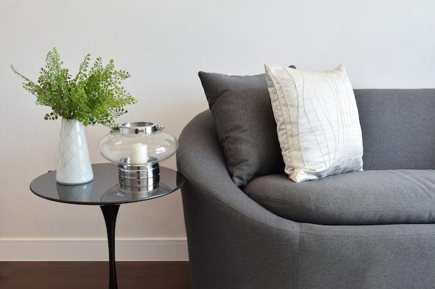 Weißes und graues dekoratives kissen auf einem zufälligen sofa im wohnzimmer