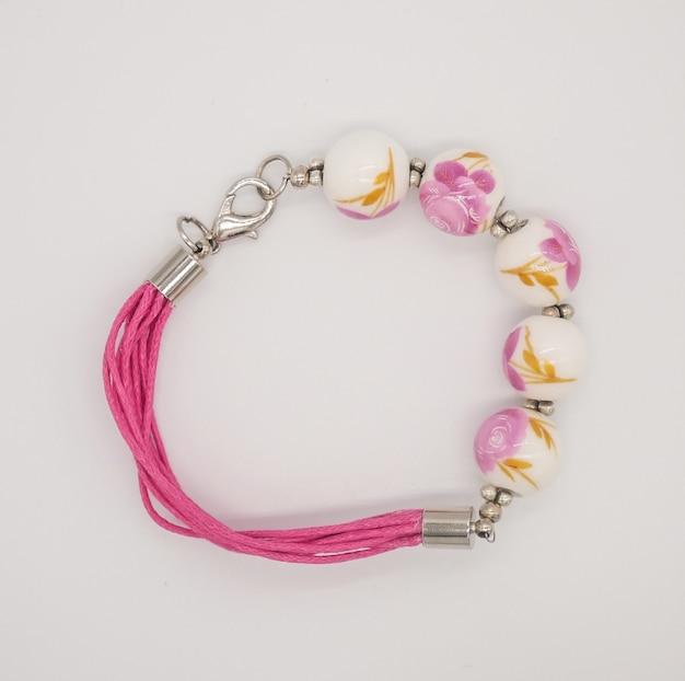 Weißes und rosa keramisches perlenarmband auf weißem hintergrund