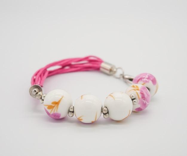 Weißes und rosa keramisches perlenarmband nah oben auf weißem hintergrund