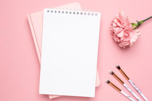 Weißes und rosa notizbuch mit gartennelkenblume und bilden bürsten auf einem rosa hintergrund