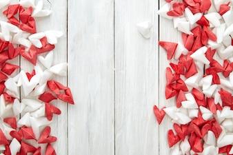Weißes und rotes Papierherz auf hölzernem