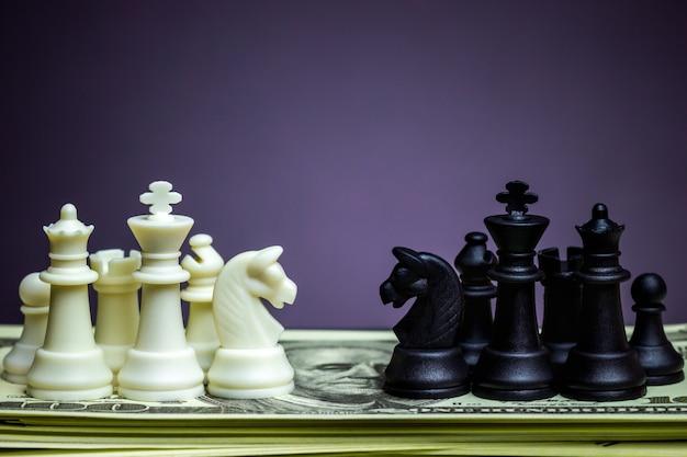 Weißes und schwarzes schach stellen sich auf einer dollarbanknote gegenüber.