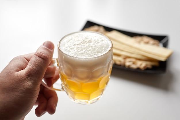 Weißes ungefiltertes bier, lange kartoffelchips, gesalzene geröstete geschälte erdnüsse in schwarzem teller