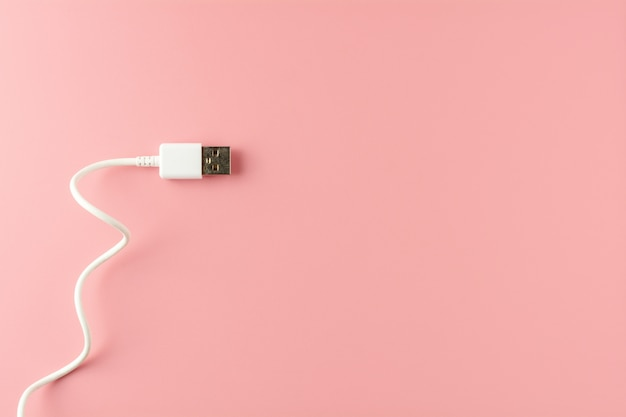 Weißes usb-kabel auf rosa hintergrund.