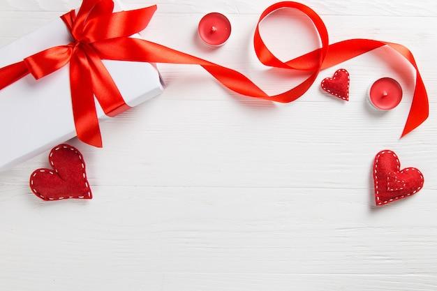Weißes verpacktes geschenk mit rotem band, kerzen und handgemachtem herzen auf dem tisch. eine romantische valentinstagsüberraschung für einen geliebten menschen.