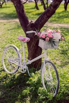 Weißes vintage fahrrad mit einem hochzeitsstrauß in einem korb