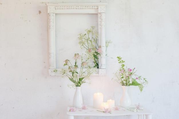 Weißes vintage interieur mit blumen und kerzen