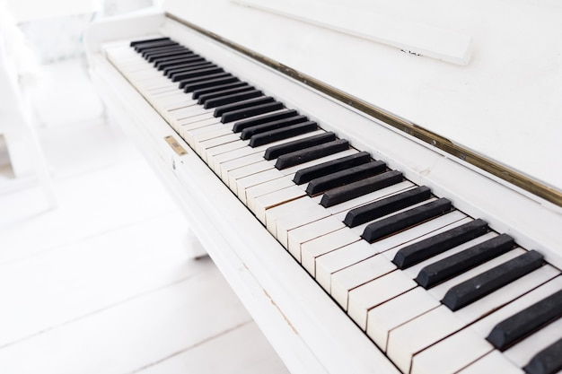 Weißes vintage klavier in einem weißen raum