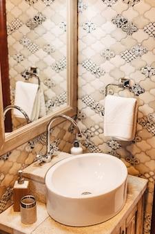 Weißes waschbecken mit großem spiegel und handtuchhalter an einer gemusterten wand
