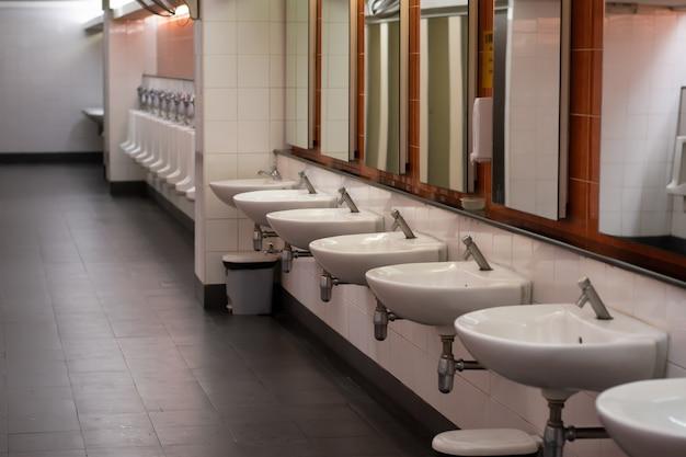 Weißes waschbecken und urinal an der wand in der öffentlichen herrentoilette.