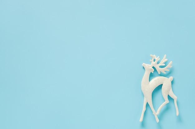 Weißes weihnachtsdekorationsrotwildspielzeug auf blauem hintergrund mit kopienraum