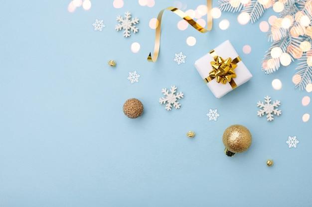Weißes weihnachtsgeschenk mit goldschleife und verzierungen auf blauem hintergrund, draufsicht. frohe weihnachten und frohe feiertage grußkarte.