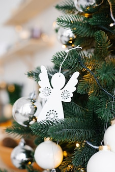 Weißes weihnachtsspielzeug auf der weihnachtsbaum-nahaufnahme