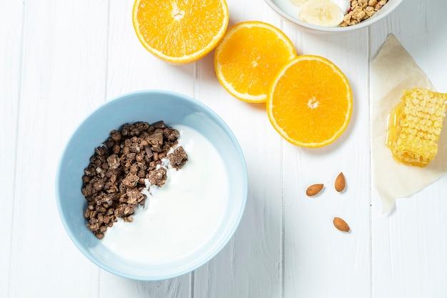 Weißes weizen- und schokoladenmüsli mit fettarmem joghurt in einer weißen schüssel in einer zusammensetzung mit einem löffel, waben, banane, orange auf weißem hölzernem hintergrund.