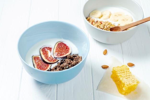 Weißes weizen- und schokoladenmüsli mit fettarmem joghurt in einer weißen schüssel in einer zusammensetzung mit einem löffel, waben, bananenfeige auf weißem hölzernem hintergrund.