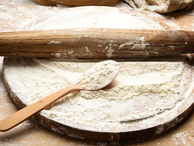 Weißes weizenmehl in einem holzlöffel, draufsicht, nahaufnahme