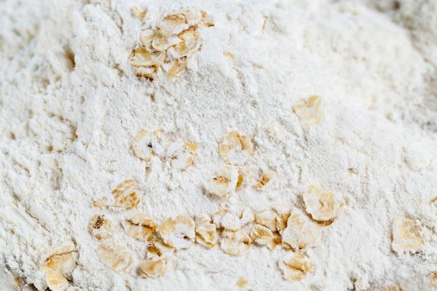 Weißes weizenmehl mit haferflocken, nahaufnahmefoto auf holzoberfläche