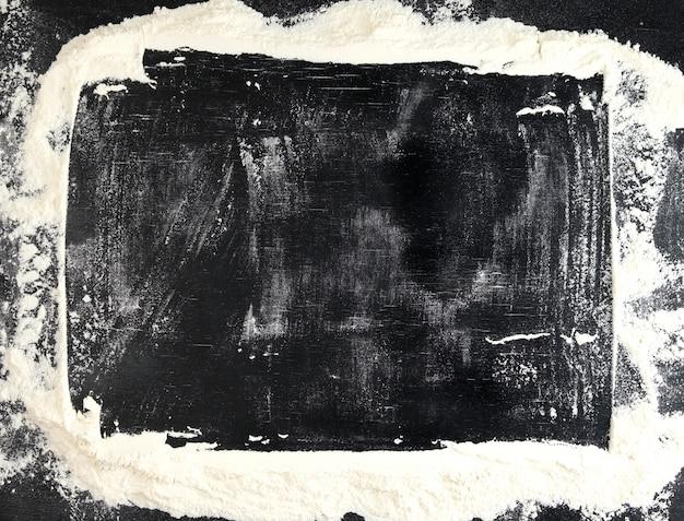 Weißes weizenmehl zerstreut auf eine schwarze tabelle