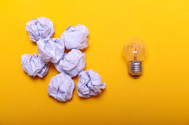 Weißes zerknittertes papier und glühlampe auf gelb