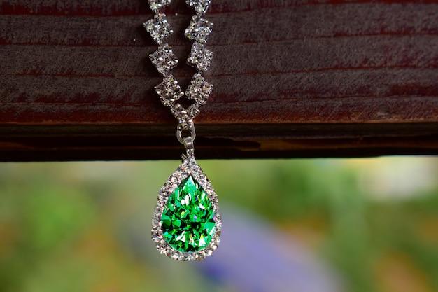 Weißgold-halskette, besetzt mit smaragd, umgeben von diamanten