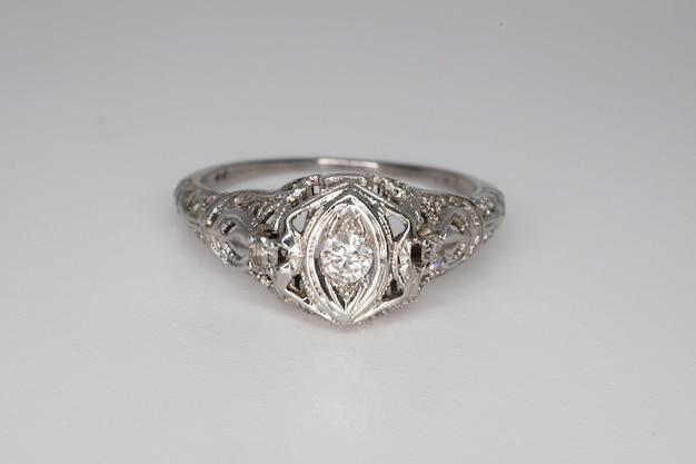 Weißgoldring mit einem diamanten auf grauem hintergrund