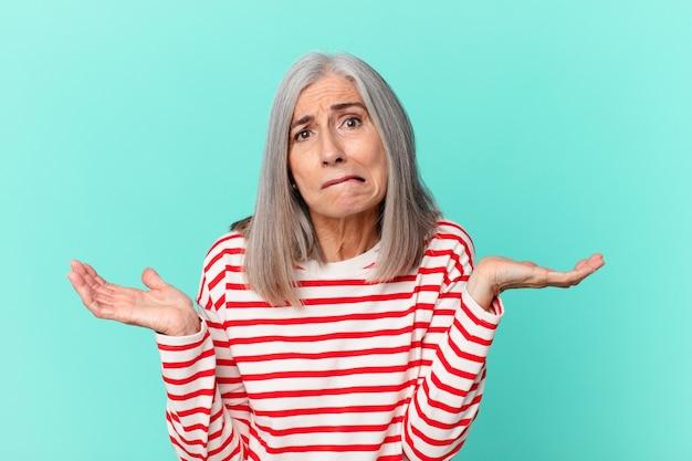 Weißhaarige frau mittleren alters, die sich verwirrt und verwirrt fühlt und zweifelt