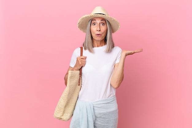 Weißhaarige frau mittleren alters, die überrascht und schockiert aussieht, mit heruntergefallenem kiefer und einem gegenstand