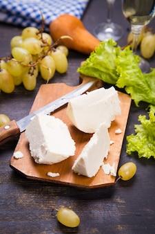 Weißkäse, trauben und salat mit weißwein