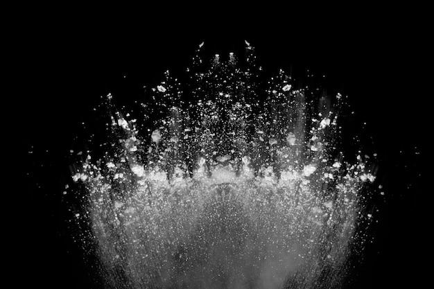 Weißpulver explosion auf schwarzem hintergrund.