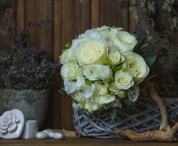 Weißrosenblumenstrauß auf rustikalen möbeln