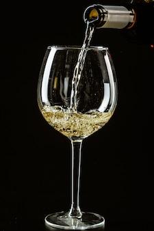 Weißwein, der in ein weinglas gegossen wird