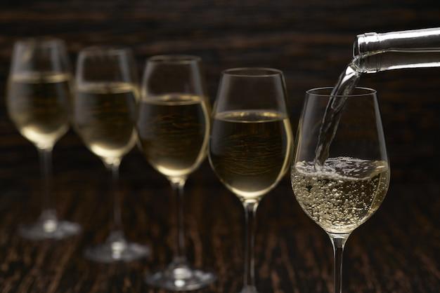 Weißwein, der in gläser von der flasche gießt