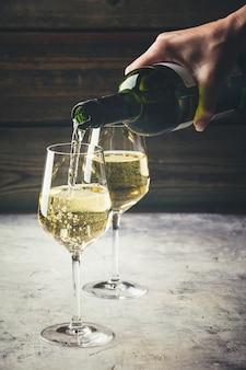 Weißwein in gläser gießen, nahaufnahme