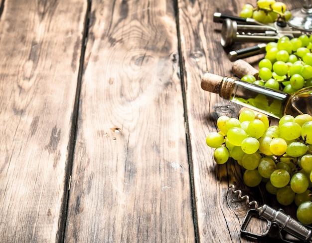 Weißwein mit einem korkenzieher und traubenzweigen auf einem holztisch